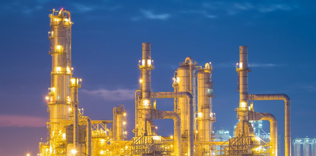Oil refinery factory at twilight with sky background.